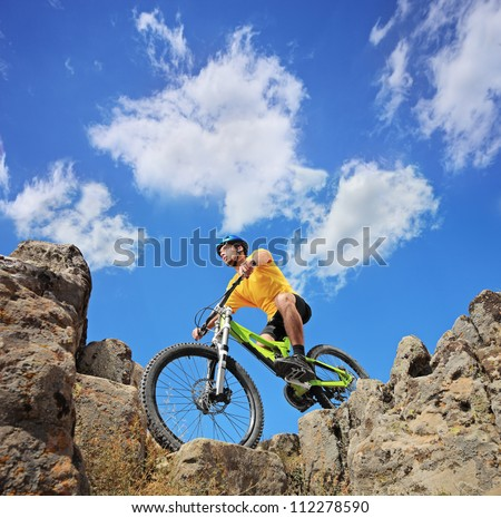A person riding a mountain bike on a sunny day, low angle view - stock photo