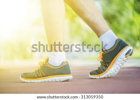 A person running outdoors on a sunny day. Only the feet are visible. The person is wearing black running shoes.Exercise, fitness and healthy lifestyle.