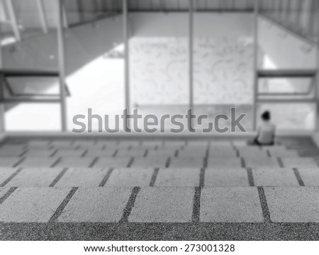 A person sitting on the steps of a modern building illustrates isolation.