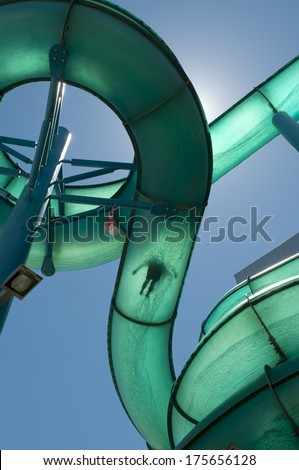 A Person sliding down a waterslide with the sun directly behind - stock photo