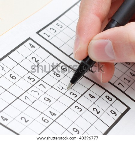 A person solving a sudoku puzzle - stock photo