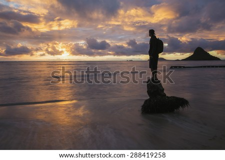 A person standing on a coconut tree stump in the shore line of Oahu's windward coast during a golden sunrise. The island known as China Man's Hat in the background.  - stock photo