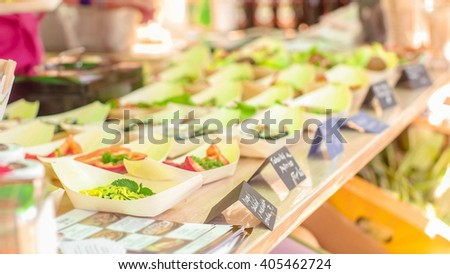 A person taking business card from the food stand with prepared raw food dishes - stock photo