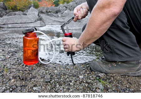 A person uses a lightweight compact water filter to pump safe drinking water - stock photo