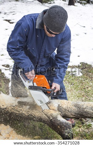 A person using a chainsaw on pretty wood - stock photo