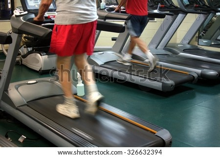 A person walking a treadmill with red shorts and a white top