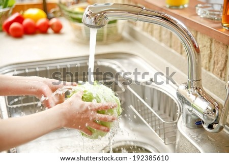 A person washing lettuce under a running tap. - stock photo