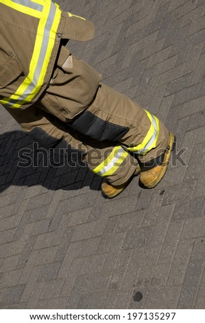 A person wearing fire fighter gear standing on brick pavers.