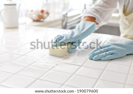 A person wearing rubber gloves scrubbing a kitchen work surface - stock photo
