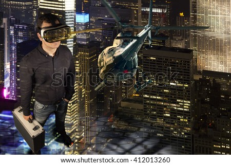 A person wears virtual reality glasses and  holds a metal suitcase in his hand. He stands in a virtual reality environment of New York at night. A helicopter flies through the scene. - stock photo