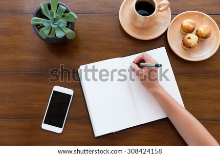A person writing on her white notebook next to her smarth phone on a beautiful new wooden table with coffee and muffins - stock photo