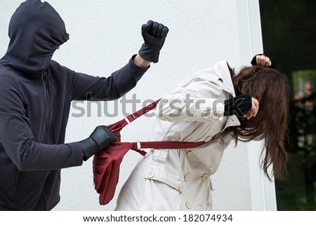 A personal assault on a passer-by with a red bag - stock photo
