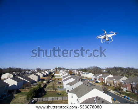 A personal drone flying through the air in a urban atmosphere.