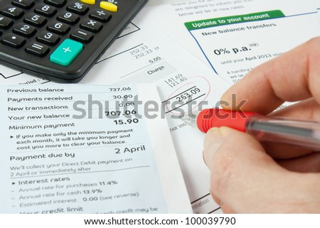 a persons hand holding a red pen and checking bank statements with a calculator - stock photo