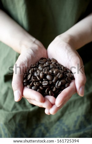 A persons hands cupped together and filled with coffee beans. - stock photo