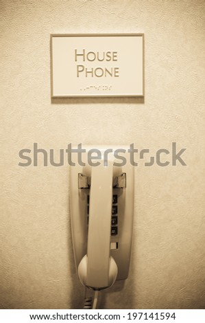 A phone on the wall with a sign above that says house phone. - stock photo
