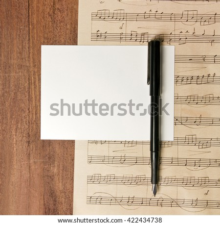 A photo of a blank white post card with copyspace, with an ink pen, on a piece of aged sheet music (piano concert), on a dark wooden background texture, shot from above; an invitation template - stock photo