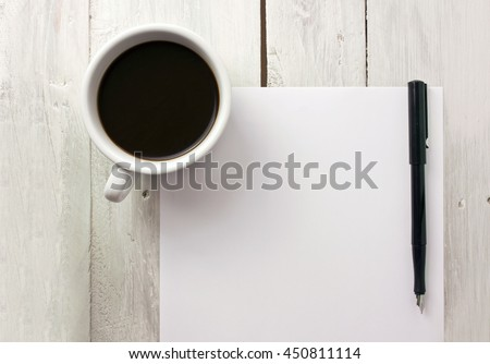 A photo of a cup of coffee with a black ink pen and a blank white sheet of paper with copyspace, shot from above on a light wooden texture; the concept of business writing or a writer's block - stock photo