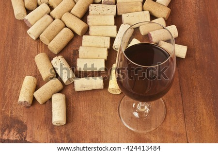 A photo of a glass of red wine with many different corks around it, on a wooden boards background texture  - stock photo
