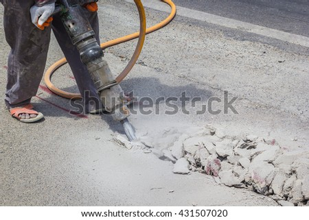 A photo of a man drilling road