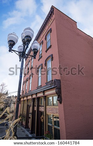 A photo of a typical small town main street building in the United States of America. Features an old brick building with am old style street lamp decorated with autumn decor.  - stock photo