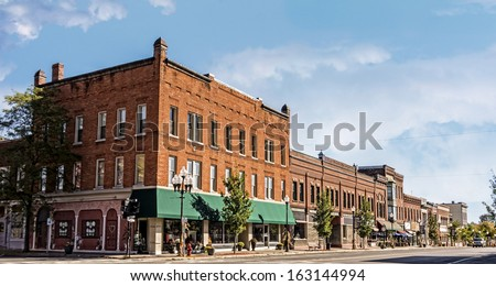 A photo of a typical small town main street in the United States of America. Features old brick buildings with specialty shops and restaurants. Decorated with autumn decor.  - stock photo