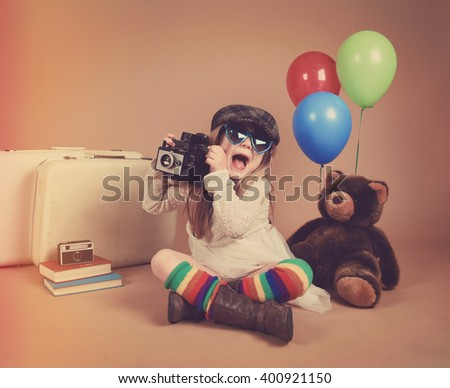 A photo of a vintage child taking a picture with an old camera against with balloons and a teddy bear for a creativity or vision concept. - stock photo