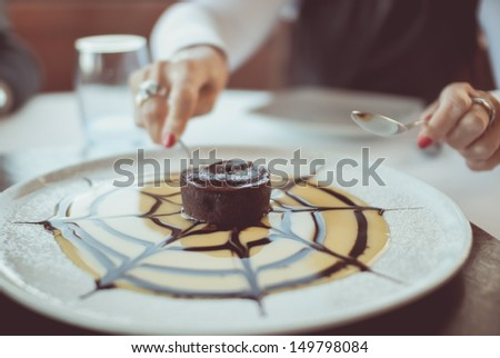 A photo of a woman's hands cutting a petit gateau small chocolate cake. - stock photo
