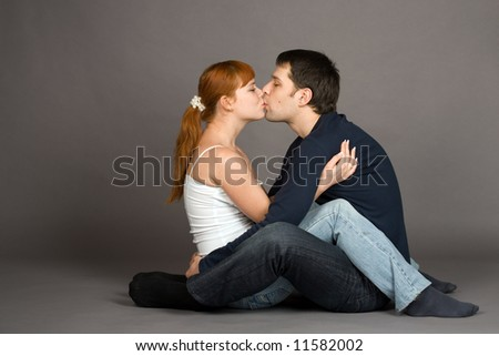 A photo of a young couple kissing, isolated on grey
