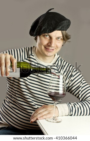 A photo of an attractive smiling Frenchman in traditional clothes (a beret and a striped sweater), pouring himself a glass of red wine from a bottle with an aerator, sitting at a white table - stock photo