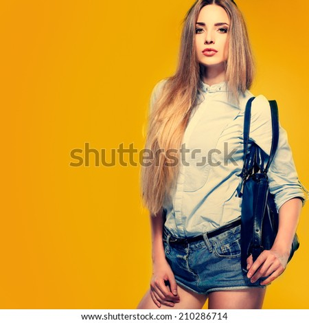A photo of beautiful girl is in fashion style on  yellow  background, glamour - stock photo