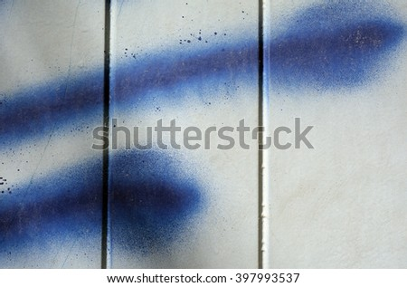 a photo of blue paint spatter on a metal door