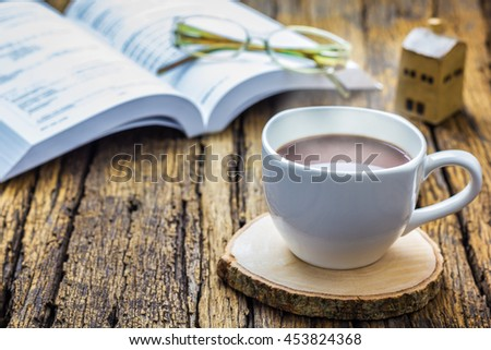 A photo of Coffee cup with book background on wood table, Selective focus, Soft focus
