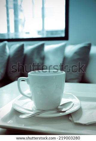 a photo of coffee in white mug on table with texture