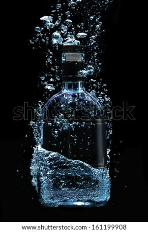 A photo of dipping luxury alcohol bottle. - stock photo