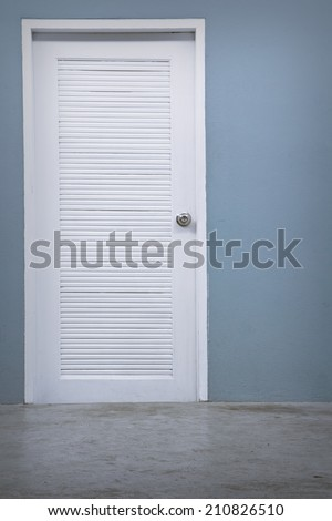 A photo of empty wall with a white door - stock photo