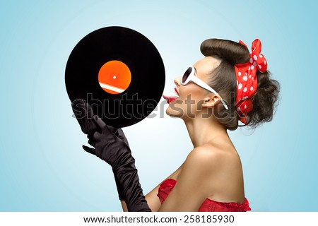 A photo of glamorous pin-up girl touching vinyl LP with tongue.