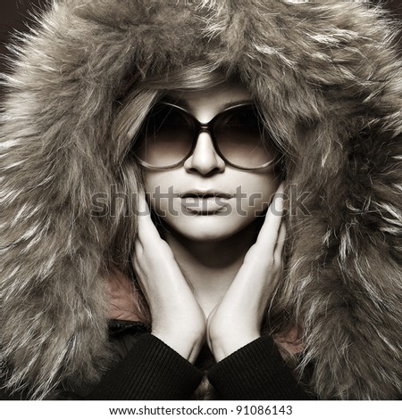 A photo of sexual beautiful girl is in fashion style in a jacket with a fur hood