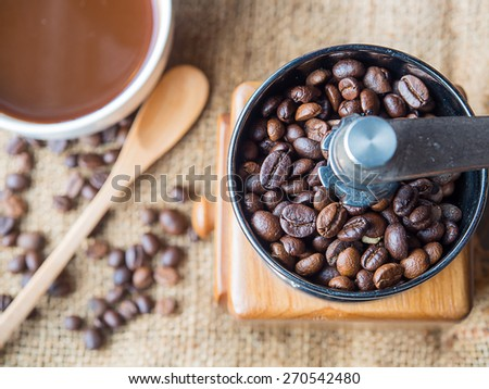 A photo of the roasted coffee beans in a coffee grinder with blur coffee beans , fresh coffee , wooden spoon on sack background. - stock photo