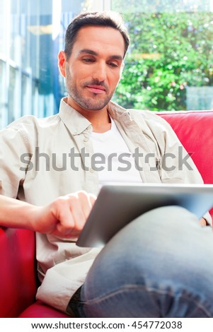 A photo of young man using digital tablet. Confident male is in casuals sitting on sofa. He is surfing the internet against window at home. - stock photo