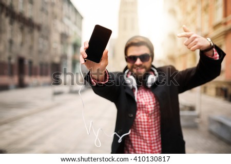 A photo of young, trendy man bragging about his mobile