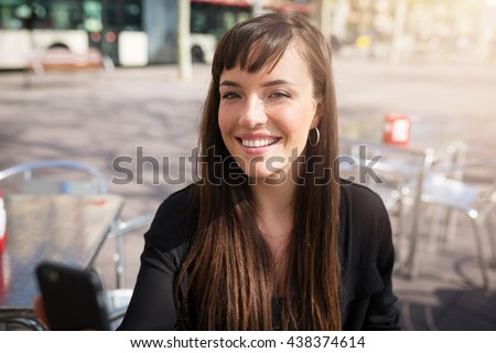A photo of young woman at the cafe garden. She's smiling happily.