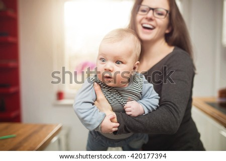 A photo of young woman holding her baby son and smiling