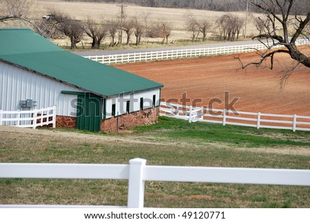 A photograph of a barn in Oklahoma surrounded by a white vinyl fence.