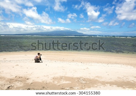 A photographer sets up a shot on a deserted beach to capture the ambiance of an empty natural wonder, with the island of Oahu outlining the horizon.  - stock photo
