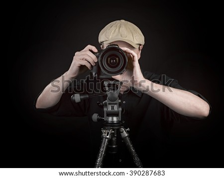 A photographer with a nice camera on black background