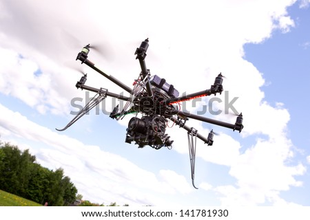 A photography multirotor helicopter with SLR camera attached - stock photo