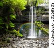 A photography of a nice rainforest waterfall in Australia with a little rainbow - stock photo