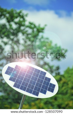 A photovoltaic Solar Panel with tree in the background. - stock photo