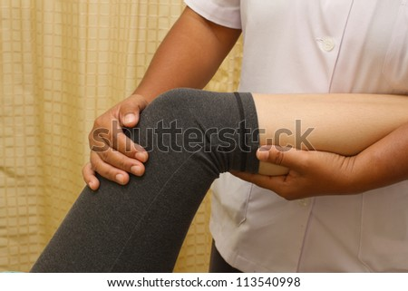 a physio therapist trying to test the knee and leg - stock photo